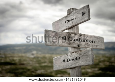 Chaos, Confusion and doubt text on wooden signpost outdoors in the wilderness. Choices, road, path, business, corporate, solution concept. #1451791049