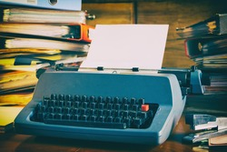 Chaos in retro office, old vintage typewriter and high stacks of folders on the desk