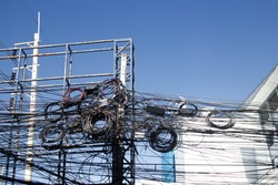 Chaos of cables and wires on electric pole, Messy wires attached to electrics pole in Bangkok, Thailand on blue sky background.