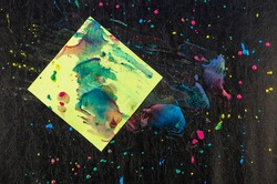 Chaotic drops of paint and piece of paper on black texture. Yellow, red, blue dots and splashes. Green square sheet of paper stained with paints. Abstract multitasking background.