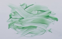Chaotically smeared green body cream on white background