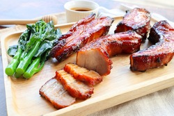 Char Siu - Honey barbecue roast pork on wood tray of wood table - Chinese style grilled pork at close up view