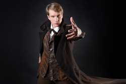 character of steampunk story, young attractive man in an elegant long coat, adventurer makes an epic gesture. intelligent gentleman in Victorian style. Vintage retro suit, young attractive man