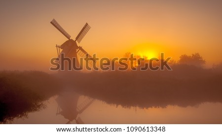 Stock Photo Characteristic historic dutch windmill along a wide canal in a polder wetland on a foggy september morning in the Netherlands