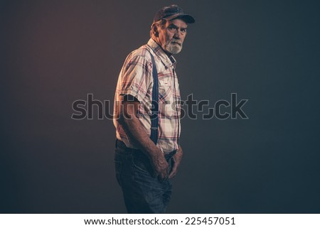 Characteristic senior man with gray hair and beard wearing blue cap with braces and jeans. Low key studio shot.