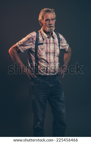 Characteristic senior man with gray hair and beard wearing checkered shirt with braces and blue jeans. Low key studio shot.