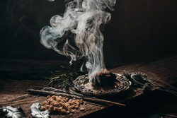 Charcoal burning with incense, incense resin, rosemary,  laurel, lavender on a rustic wooden table,smudging, energetic cleansing and smoking.Sahumar