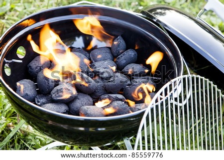 charcoal fire inside a barbeque in green grass