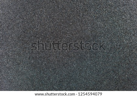 Charcoal grey colored sand paper textured background with sparkles and glitters #1254594079