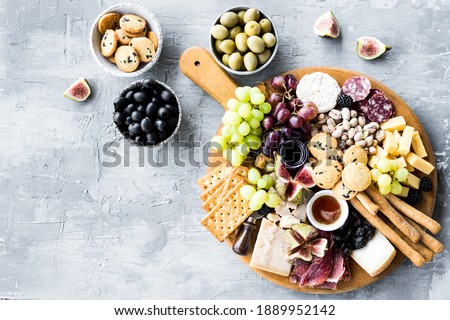 Charcuterie board. Cheese platter: Parmesan, maasdam, camembert, cheddar, gouda with prosciutto, salami, fruits and nuts. Assortment of tasty appetizers or antipasti. Top view. Copy space. Stock photo ©
