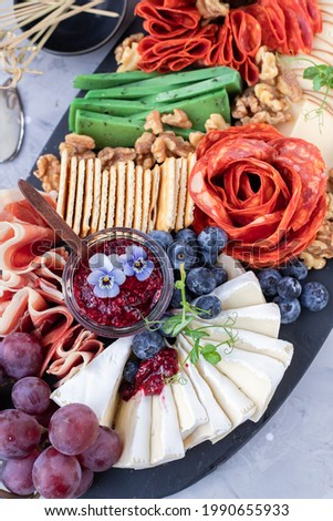 Charcuterie board with meat, nuts and  cheese varieties, raspberry jam and edible flowers. Close up