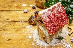 Charcuterie chalet or The Meat Hut as Christmas newest food trend. New Year Keto gingerbread house with traditional decor and symbols. Festive wooden boards background, copy space