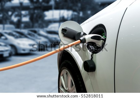 Charging an electric car with the power cable supply plugged in. #552818011