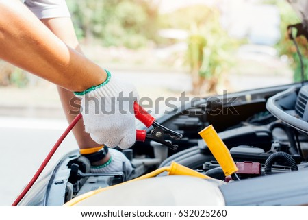Charging battery car with electricity trough jumper cables,copy space. #632025260