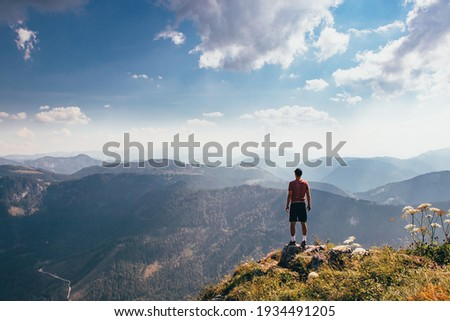 Charging energy in wild Austrian nature. Athlete of lighter figure with cap and red elastic trick stands on the edge of rock and enjoys feeling of relaxation and freedom. Conquering Mount Otscher. Foto d'archivio ©