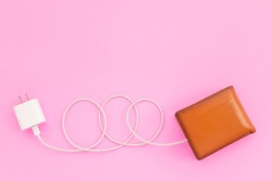 Charging the power to financial concept : Top view white charger cable connect to brown wallet on pink background