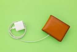 Charging the power to financial concept : Top view white charger cable connect to brown wallet on green background