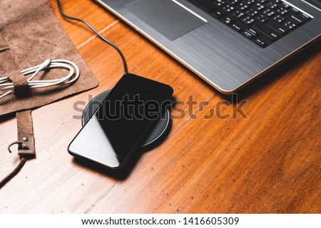 Charging the smartphone with wireless charger on wooden desk. Photo stock ©