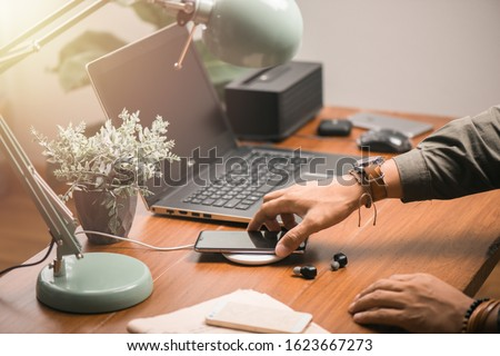 Charging the smartphone with wireless charger on wooden desk. Modern lifestyle concept. Stockfoto ©