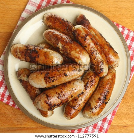 Chargrilled pork sausages piled in a plate.
