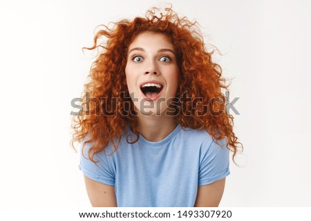 Charismatic beautiful redhead woman with curly hairstyle, making surprising and amused expression, widen eyes astonished open mouth surprised, standing white background impressed #1493307920