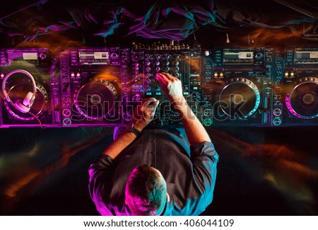 Stock Photo Charismatic disc jockey at the turntable. He plays on the best, famous CD players at nightclub during party. Party EDM concept.