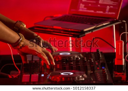 Charismatic disc jockey at the turntable in concert. DJ plays on the best, famous CD players on stage. EDM, party concept.