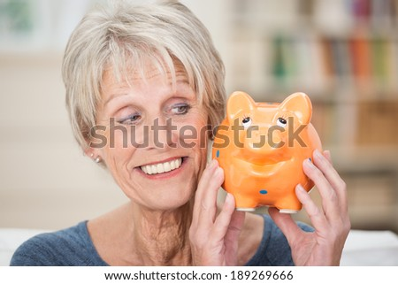 Charismatic elderly woman holding up a piggy bank looking sideways at is as she smiles while contemplating what to do with her savings