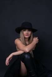 charismatic girl in dark dress and hat posing on black background.