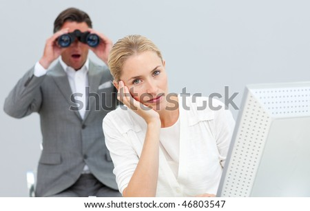 Charismatic manager holding binoculars looking at his colleague's computer in the office