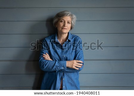 Charismatic person. Serious elderly latin lady posing for portrait keep arms crossed. Confident old female mother grandma in stylish jeans jacket stand by grey planked wall look at camera. Copy space