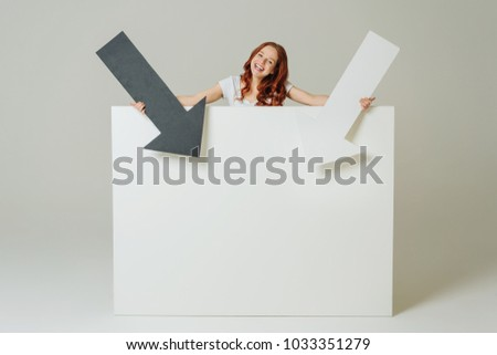 Charismatic smiling woman pointing to a large blank white signboard with copy space with two arrows over a neutral studio background #1033351279
