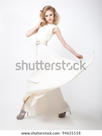 Charismatic young lovely female blond hair with flying vernal dress isolated over white background