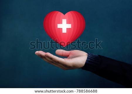 Charity and Donation Concept, Red Heart with Cross floating over Opened Hand