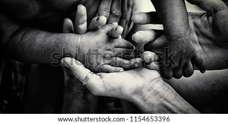 Charity. Close up of diverse people holding hands together. Concept of adopting little children from Africa. Volunteer's programs for helping in poor African counties. Global world problems. Help