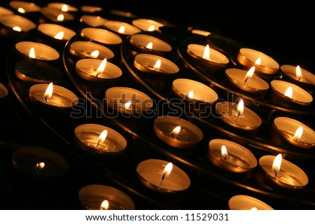 Charity. Lignting of Praying candles in a temple.