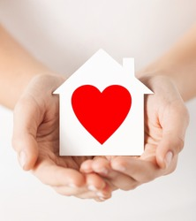 charity, real estate and family home concept - closeup picture of female hands holding white paper house with red heart