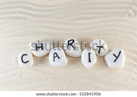 Charity word on group of stones with sand background