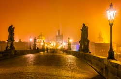 Charles Bridge and the towers of the old city of Prague on fog, Czech Republic