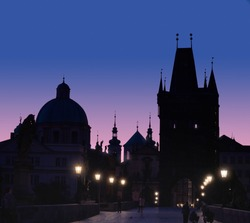 Charles Bridge at dawn. Panoramic image, silhouette of Bridge Tower and saint sculptures with street lights in Prague, Czech Republic.