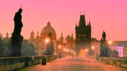 Charles Bridge at dawn, silhouette of Bridge Tower and saint sculptures with street lights in Prague, Czech Republic
