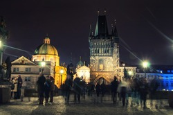 Charles bridge in Prague, Czech Republic at night with blurred people. Lens flare, street lamps light and illumination