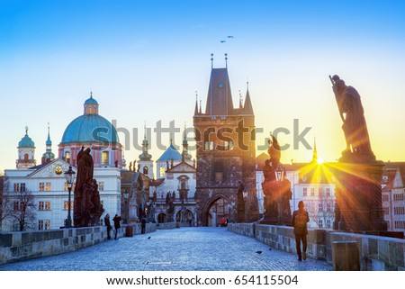 Charles bridge sunrise scenery, sun rays visible. Prague iconic travel destination, Czech Republic.   #654115504