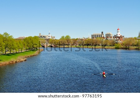 Charles River in the spring. People rowing, jogging, walking� Harvard University buildings in the background.
