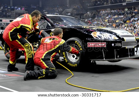 CHARLOTTE, NC - MAY 14: Cheerios front tire changer Clint Pittman and tire carrier Shane Stevenson compete in the NASCAR Pit Crew Challenge at Time Warner Cable Arena on May 14, 2009 in Charlotte, NC. - stock photo