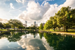 Charlotte, North Carolina skyline with the reflection of the clouds and buildings in the water. Taken from Marshall park.