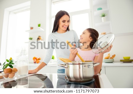 Charming adorable attractive beautiful caucasian kind young smiling mum and her small little offspring daughter having fun, praparing vermicelli in light kitchen #1171797073