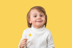 Charming adorable little boy smiling with dimples looking at camera, holding lollipop. Child isolated on yellow background, copy space.