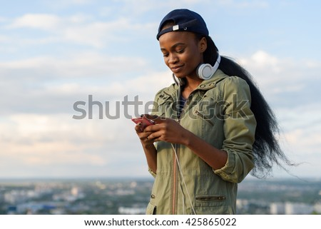 Charming african american girl listen to music and relaxing. Smiling young black lady on blurred city background