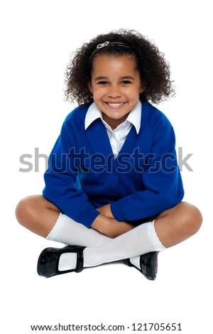 Charming African school girl flashing a smile. Studio shot - stock photo